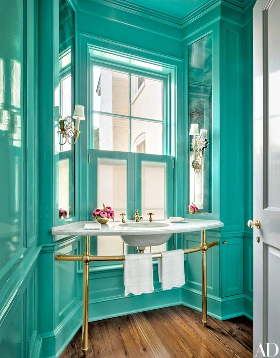 a refined vintage bathroom all painted in turquoise, with a free-standing sink and touches of gold looks very chic