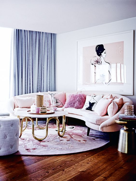 a romantic living room with a blush curved sofa and a matching artwork, blue curtains and an ottoman, a printed floral round rug