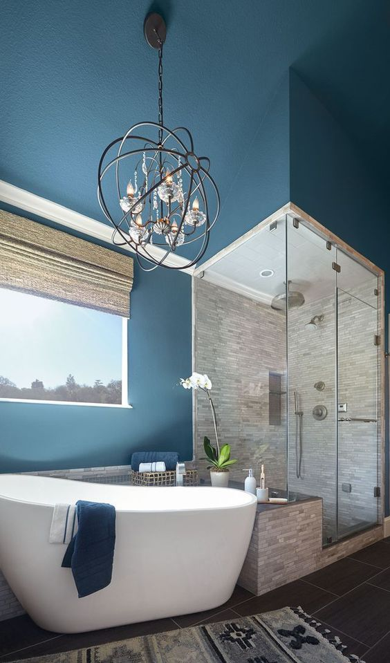 a royal blue painted bathroom with a neutral shower space,a  tub and a vintage chandelier