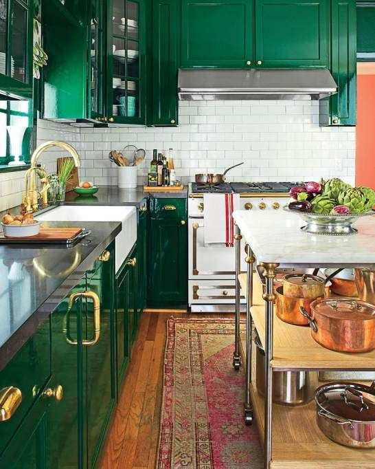a shiny glam emerald kitchen, a white subway tile backsplash, black countertops and gold and brass touches