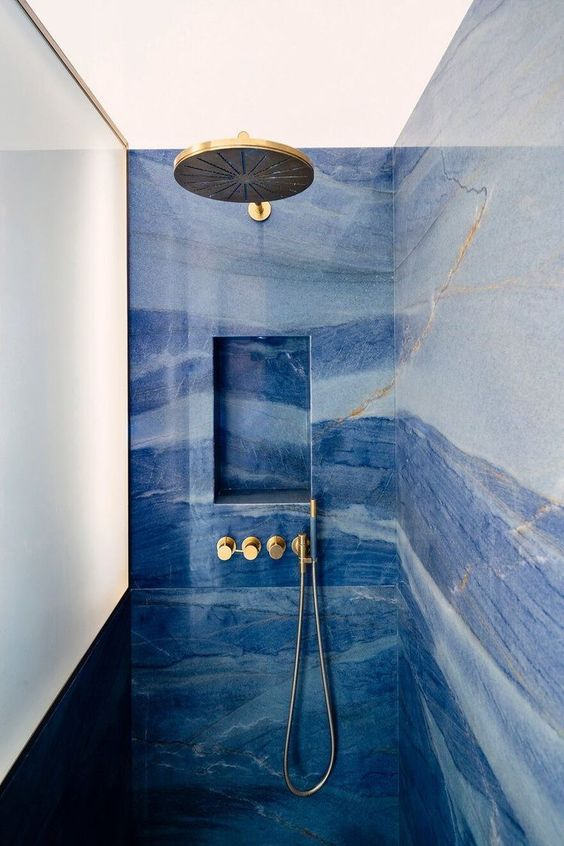 a shower space done with blue marble tiles and touches of gold looks just jar-dropping