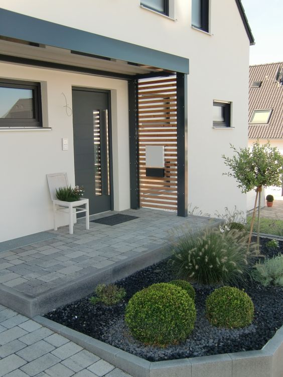 a simple and modern porch with a wood slab screen and a white chair planter looks cool and stylish
