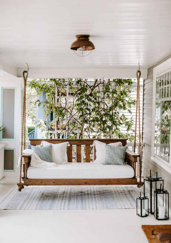 a simple and neutral summer porch with a hanging daybed with pillows, a striped rug and candle lanterns