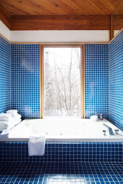 a simple and welcoming bathroom fully clad with royal blue mosaic tiles that make a throwback to the 70s