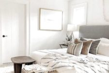 a simple neutral bedroom with a grey bed, wooden stools, printed linens, artworks and a faceted lamp