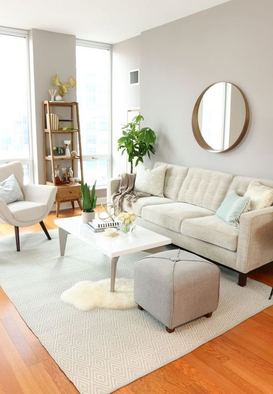 a simple neutral living room with neutral upholstered furniture, a white table, layered rugs and a wooden shelf