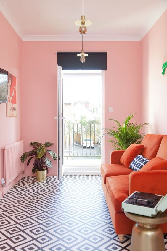 a small bright living room with pink walls, an orange sofa, a gallery wall and potted plants for more glam