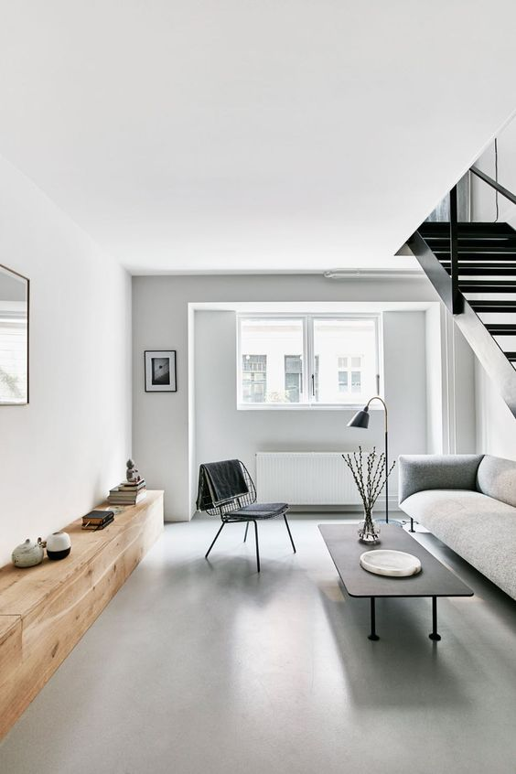 a small minimalist living room with a grey sofa, a black table and chair and a long wooden sideboard