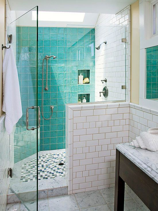 a small modern bathroom in neutrals, with turquoise tiles in the shower, a skylight and two types of white tiles