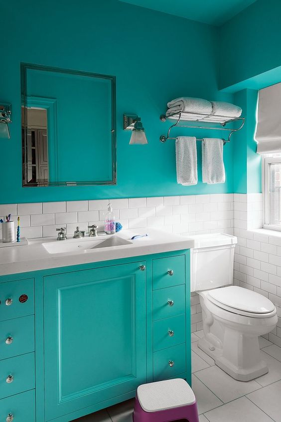 a small modern bathroom with turquoise walls, white subway tiles, a turquoise vanity and white appliances