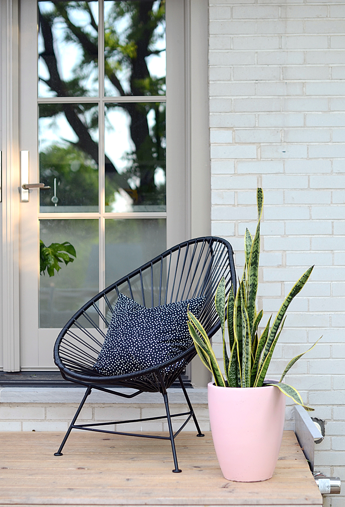 a small modern porch with a black woven chair, a printed pillow and a statement plant in a pink pot