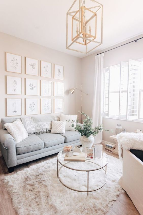 a small neutral living room with a gray sofa, a glass table, a gallery wall and a gold framed chandelier