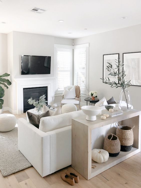 a small neutral living space with a white sofa and chairs, a built in fireplace, a console and some accessories