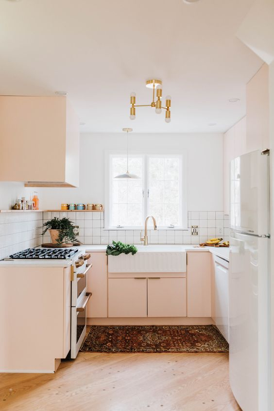 a small yet chic kitchen in blush and white, with a gold chandelier, a white tile backsplash and white countertops