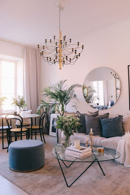a soft living-dining room with blush walls, a round mirror, a chic chandelier, touches of grey and navy
