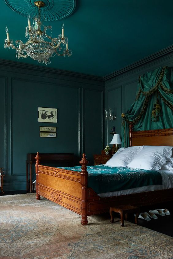 a sophisticated bedroom with dark green walls and a ceiling, a green canopy and bedding is moody and chic