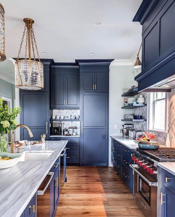 a statement blue kitchen with a marble tile backsplash, stone countertops and catchy pendant lamps and sconces