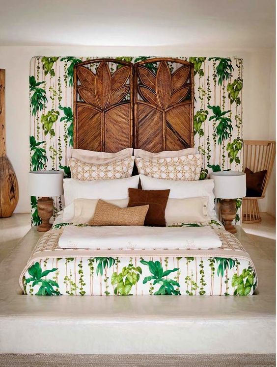 a statement boho tropical bedroom with a wooden carved screen, a platform bed, wooden lamps and printed bedding