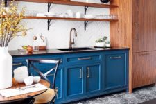 a stylish bistro-inspired kitchen with blue cabinets, a white tile backsplash, black countertops and wooden shelves