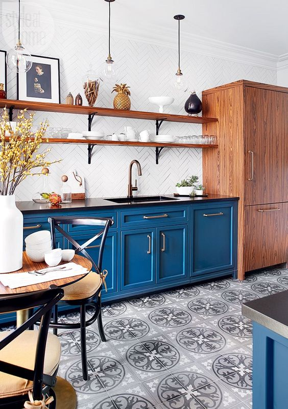 a stylish bistro inspired kitchen with blue cabinets, a white tile backsplash, black countertops and wooden shelves