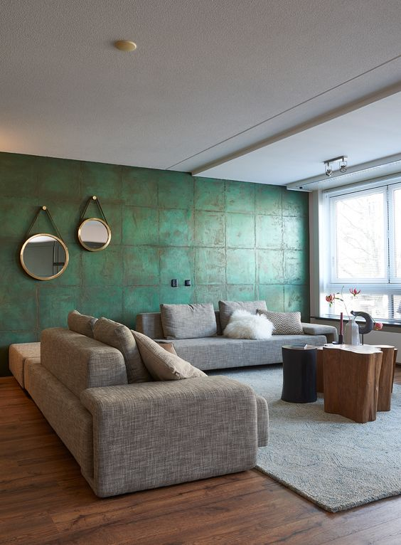 a stylish contemporary living room with a green tile wall, a grey sectional, a wood stump table and a large window