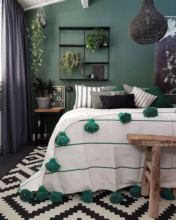 a stylish eclectic bedroom with a green accent wall, wooden and metal furniture, a woven pendant lamp and touches of green textiles