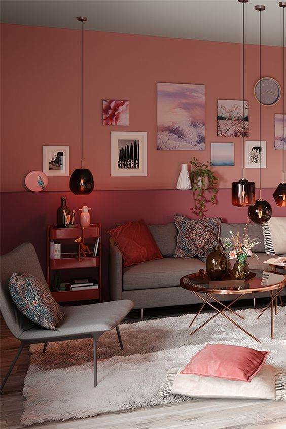 a stylish living room with a color block pink and purple wall, a gallery wall, grey seating furniture and pendant lamps