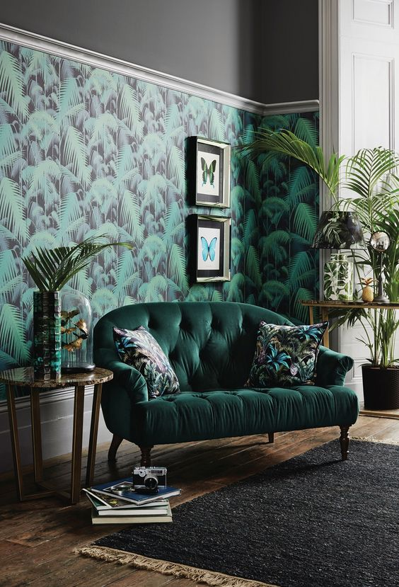 a stylish living room with a tropical leaf wall, a hunter green sofa, potted greenery and artworks