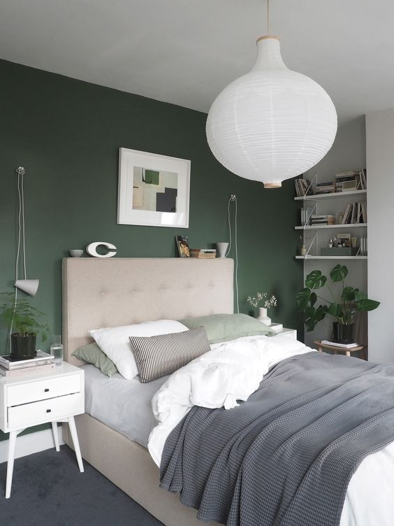 a stylish modern bedroom with a hunter green accent wall, neutral furniture and some potted greenery