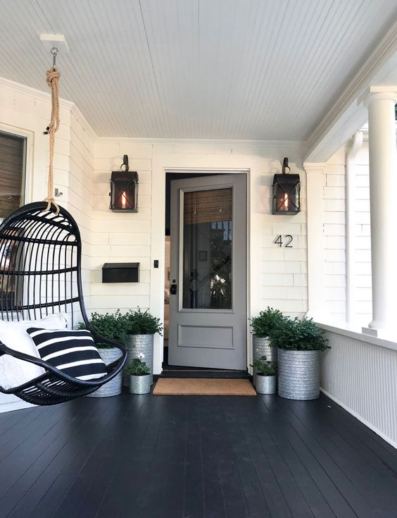 a stylish modern black porch with potted greenery in metal planters, a black suspended chair with graphic pillows and lanterns