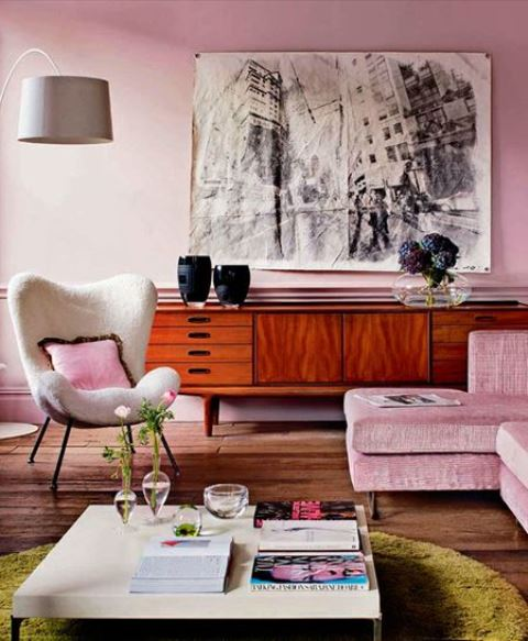 a stylish modern living room with light pink walls and a matching sofa, a graphic artwork and a rich toned credenza
