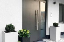 a stylish modern porch with a blakc metal door, grey and black tall square planters with greenery