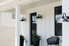 a stylish monochromatic porch with a black chair, a white side table, some cotton, black planters with ferns and sconces