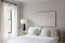 a stylish neutral bedroom with an upholstered bed, simple nightstands, black lamps and a statement artwork