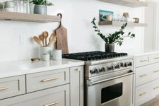 a stylish neutral kitchen in creamy and dove grey cabinets, wooden floating shelves and a white hood