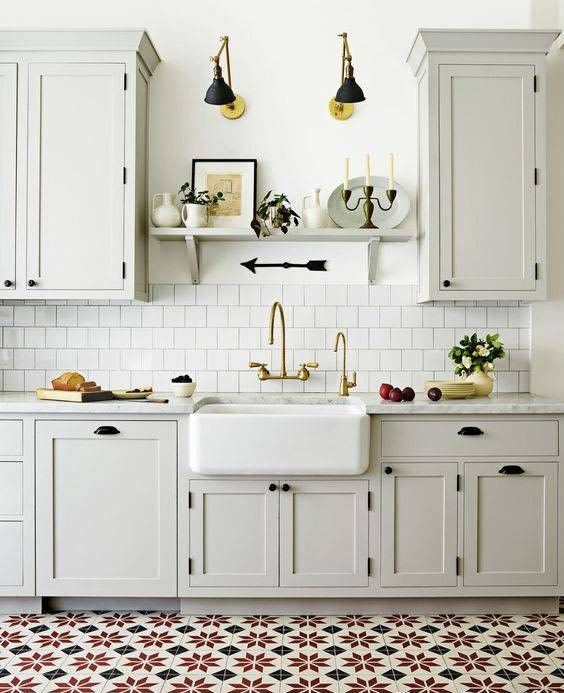 a stylish neutral kitchen in dove grey, with white tiles, open shelves, sconces and a patterned tile backsplash
