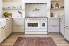 a stylish neutral kitchen with dove grey cabinets, a large white hood, a white cooker, built-in shelves and a printed rug