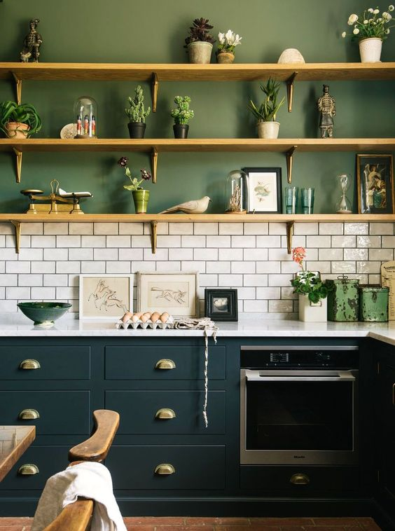 a stylish two tone kitchen with green walls, hunter green cabinets and a white tile backsplash to refresh