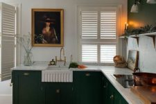 a stylish vintage-inspired kitchen in emerald, with a white marble backsplash and countertops and gold touches