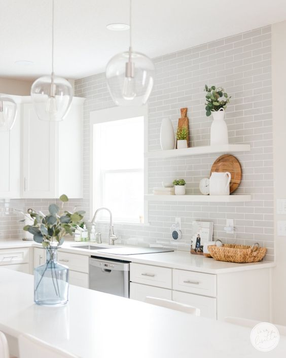 a stylish white and dove grey kitchen with subway tiles, simpel cabinets, pendant lamps and floating shelves