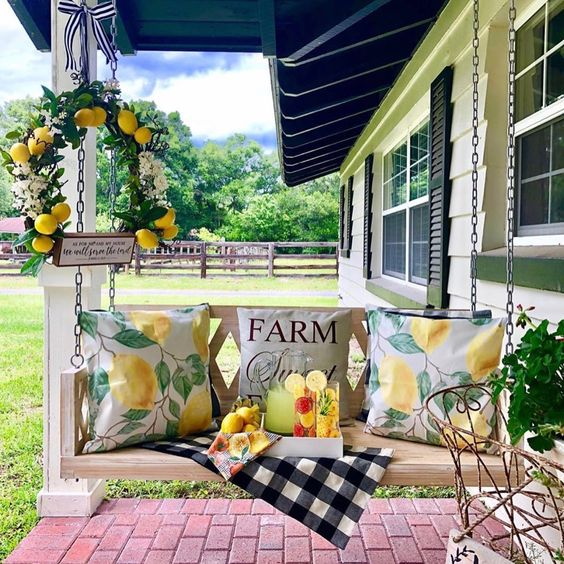 a summer farmhouse porch with a hanging bench, bright citrus print pillows, a citrus wreath and some drinks on a tray