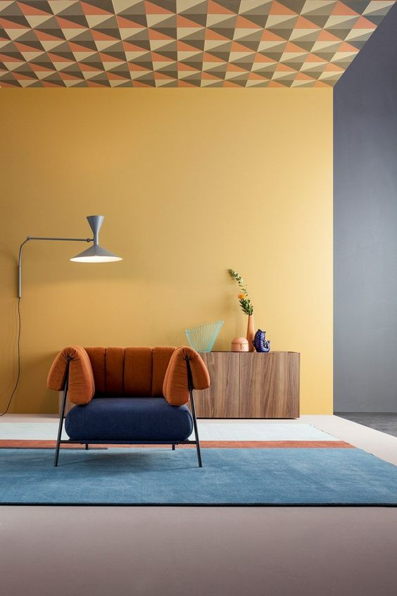 a super bold contemporary space with a yellow wall, a two tone chair, a color block rug and some bright accessories