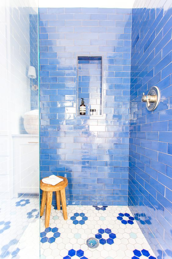 a super bright blue bathroom with subway tiles, mosaic hex tiles on the floor and a wooden stool