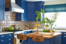 a super bright blue kitchen with a patterned tile backsplash, white countertops and vintage wooden chairs