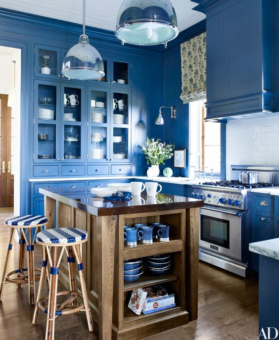 a super bright blue kitchen with a white subway tile backsplash, pendant lamps, a printed shade and a wooden kitchen island