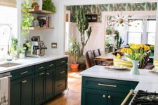 a super catchy boho kitchen with hunter green cabinets, white countertops, gold handles and open shelving