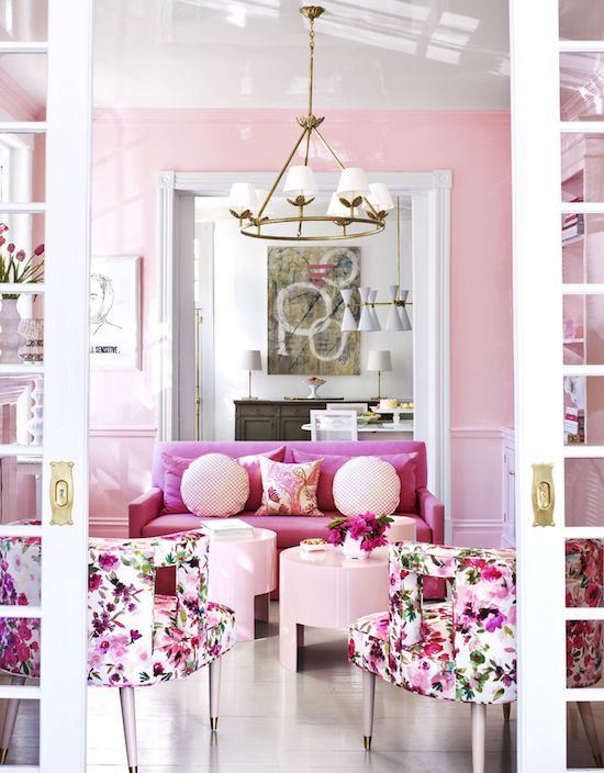 a super feminine living room with light pink walls, a hot pink sofa, light pink tables and floral chairs