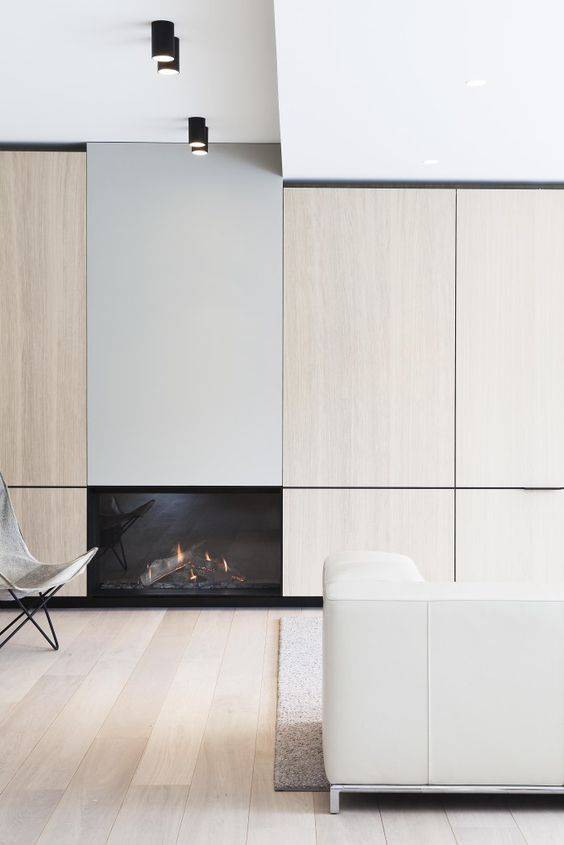 a super minimalist neutral living room with hidden storage, a built-in fireplace and comfy furniture