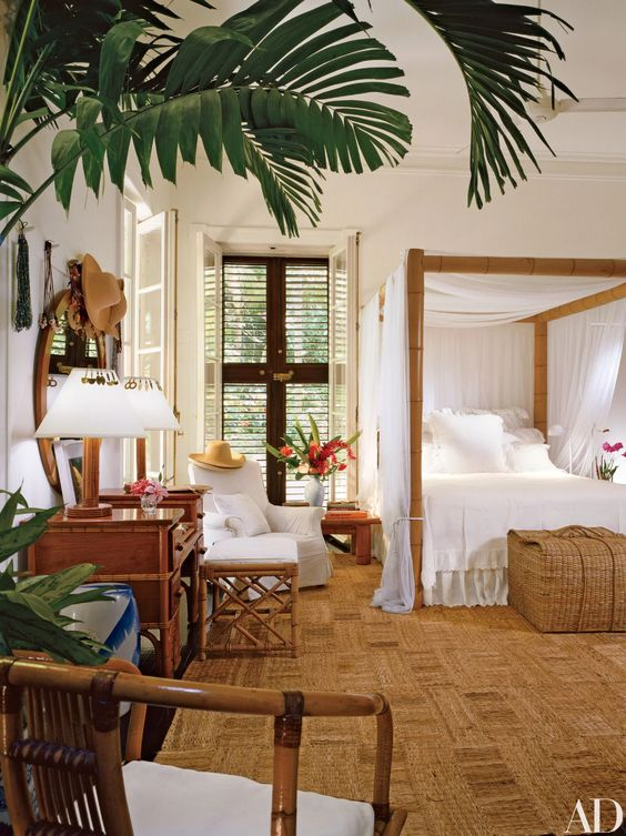a tropical bedroom with a jute rug, a bamboo bed with a canopy, wooden furniture and shutters plus tropical plants