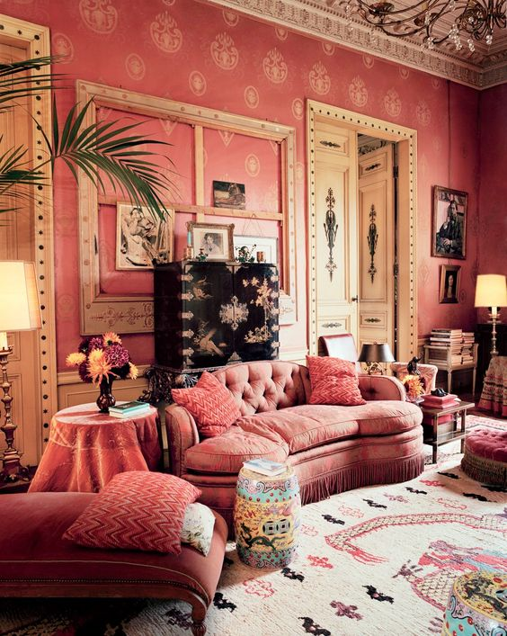 a unique refined living room with pink wallpaper walls, pink furniture, incusted doors, a gallery wall and lots of books